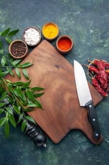 ダークブルーの表面色の木製の鋭いカトラリーツリーグリーンキッチンに茶色の木製デスクを備えたさまざまな調味料の上面図