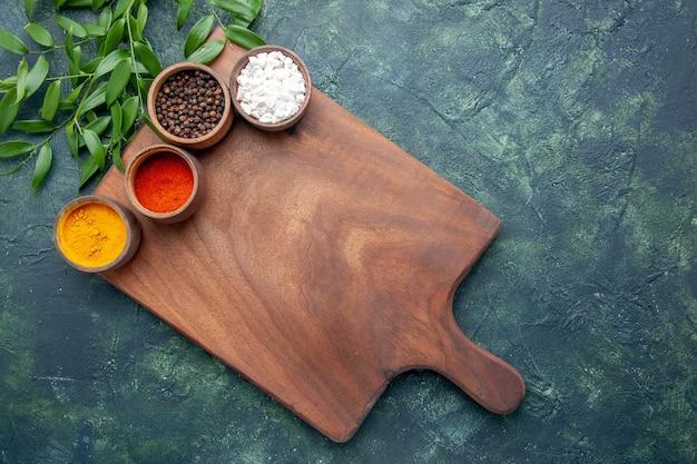 진한 파란색 표면 색상 날카로운 칼 붙이 나무 녹색 부엌에 갈색 나무 책상과 상위 뷰 다른 조미료