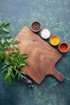 ダークブルーの表面色の木製キッチンシャープなカトラリーツリーグリーンに茶色の木製デスクを備えたさまざまな調味料の上面図