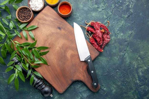 ダークブルーの背景色の木製の鋭いカトラリーツリーグリーンキッチンに茶色の木製の机とさまざまな調味料の上面図 無料写真