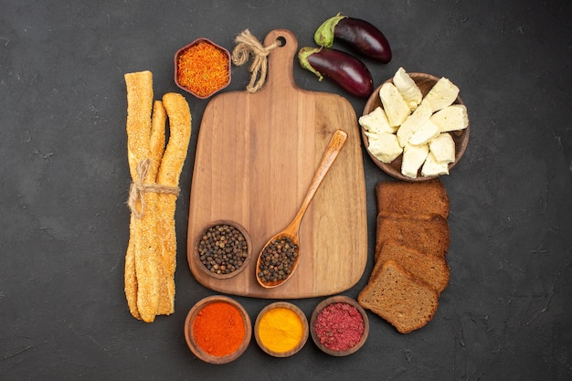 Top view of different seasonings with cheese and black bread loafs on black Free Photo