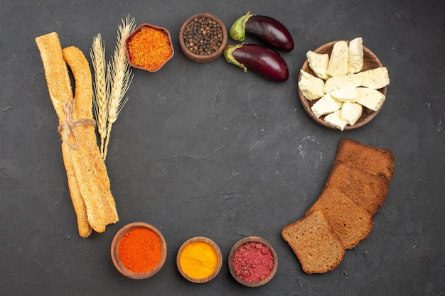 Top view of different seasonings with cheese and black bread loafs on black