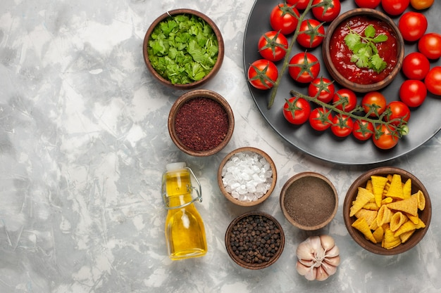 Vista dall'alto diversi condimenti con pomodorini e olio sulla scrivania bianca