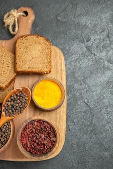 Вид сверху разные приправы с буханками темного хлеба на серой поверхности, острый, горячий хлеб