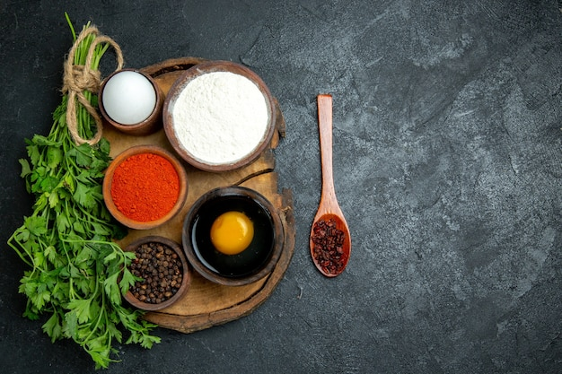 Top view different seasonings with egg and flour on grey space