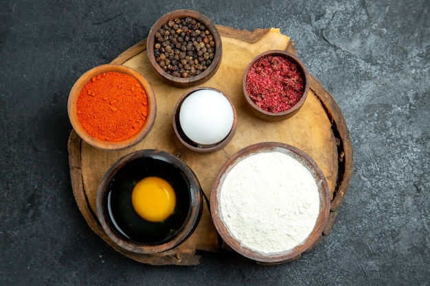 Top view different seasonings with flour and egg on grey space