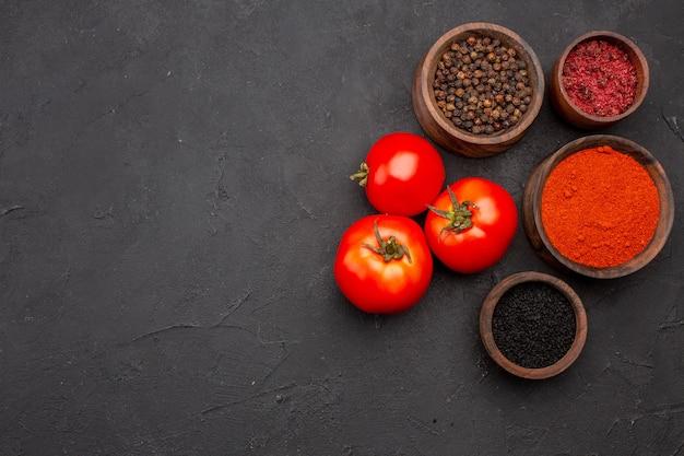 暗い背景の食事サラダ健康調味料に新鮮な赤いトマトとさまざまな調味料の上面図