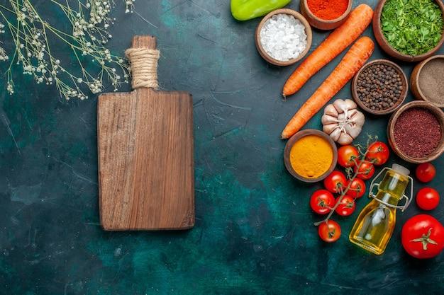 ダークグリーンのデスクにフレッシュトマトを使ったさまざまな調味料の上面図材料製品食事食品野菜