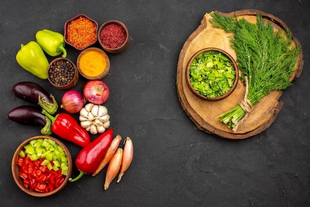어두운 배경의 익은 야채 샐러드에 신선한 야채와 채소를 곁들인 다양한 조미료