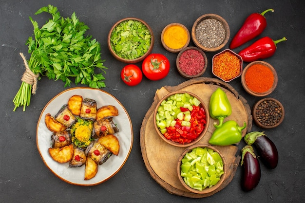 Vista dall'alto di diversi condimenti con verdure fresche sul tavolo nero