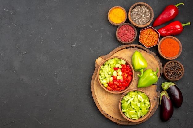 Vista dall'alto di diversi condimenti con verdure fresche su nero
