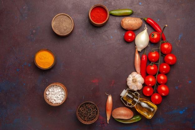 Top view different seasonings with fresh vegetables on dark-purple space