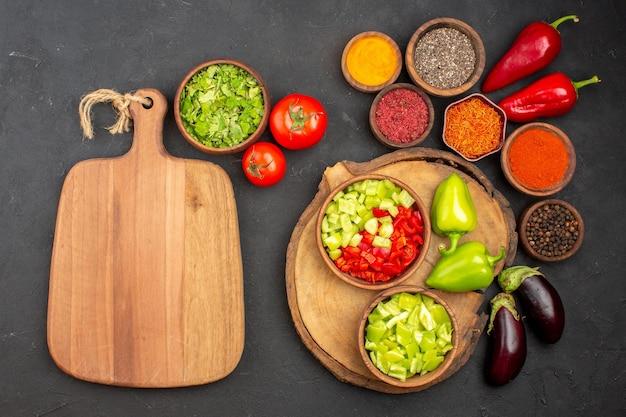 Vista dall'alto di diversi condimenti con verdure fresche al buio
