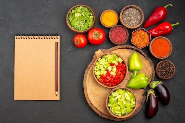 Top view of different seasonings with fresh vegetables on dark