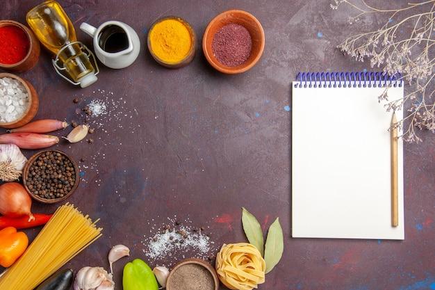 暗い机の上に新鮮な野菜を使ったさまざまな調味料の上面図スパイシーペッパーフードサラダの健康