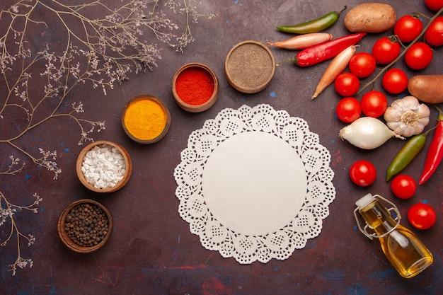 暗い机の上に新鮮な野菜とさまざまな調味料の上面図