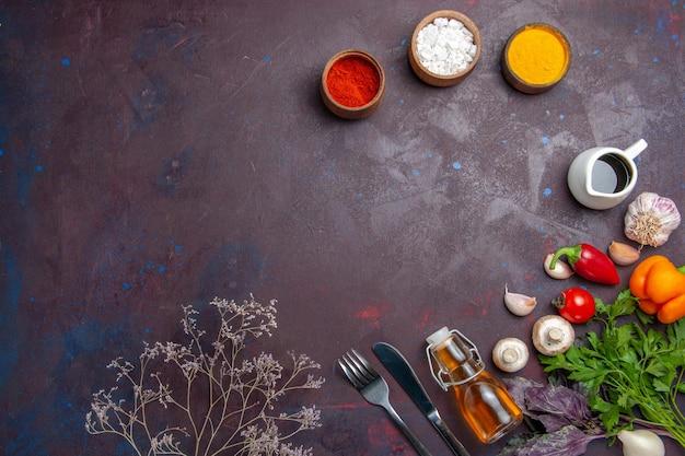 暗い表面の食品スパイシーペッパーサラダの健康に新鮮な野菜を使ったさまざまな調味料の上面図