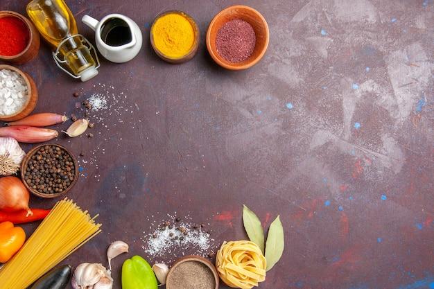 暗い背景に新鮮な野菜を使ったさまざまな調味料の上面図スパイシーペッパーフードサラダの健康