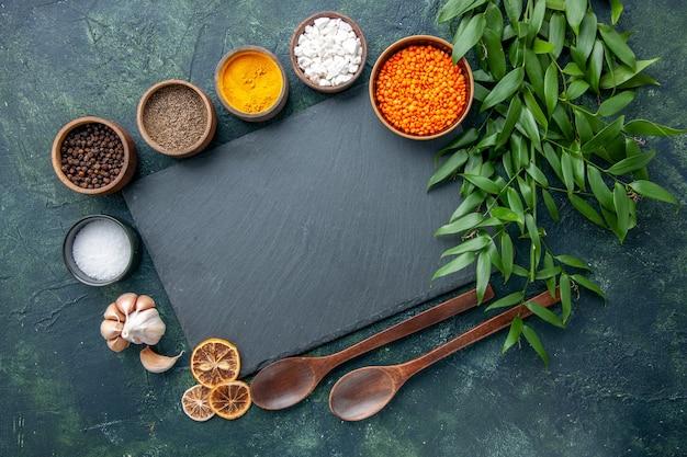 トップビューダークブルーの背景にニンニクとオレンジのレンズ豆を使ったさまざまな調味料写真食品スパイシーな唐辛子色の鋭い種子のスープ