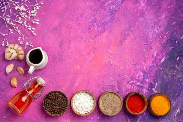 ピンクのテーブルスパイスペッパーの色にニンニクとさまざまな調味料の上面図