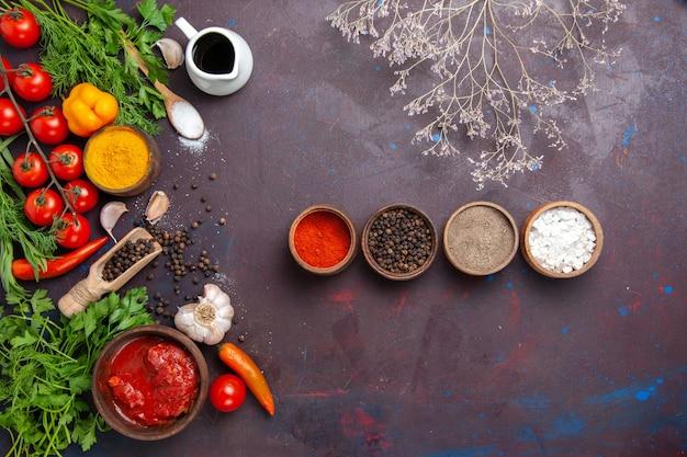 暗い机の上に緑と野菜を使ったさまざまな調味料の上面図
