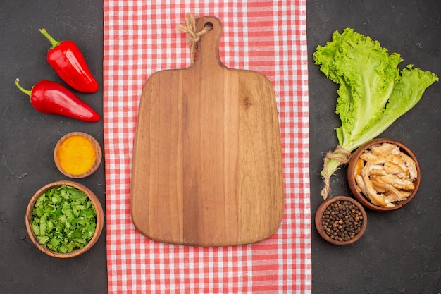Top view of different seasonings with greens on black
