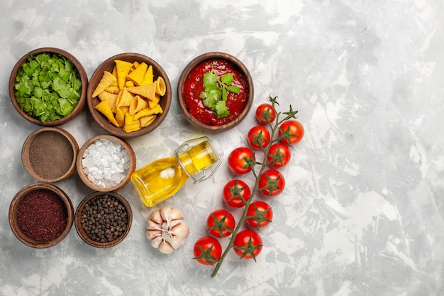 Vista dall'alto diversi condimenti con pomodori verdi e olio sulla scrivania bianca