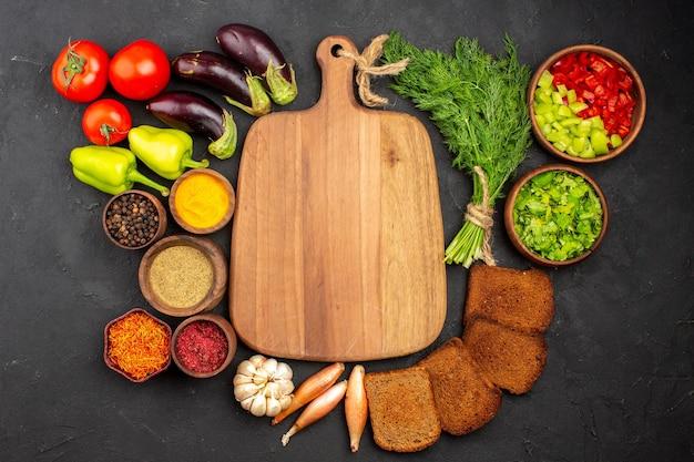 暗い背景に緑の野菜と暗いパンのパンとさまざまな調味料の上面図サラダ調味料パン健康食品