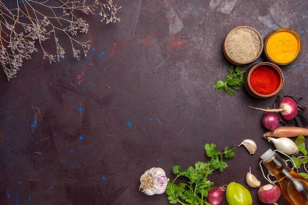 Vista dall'alto di diversi condimenti con verdure e verdure su nero