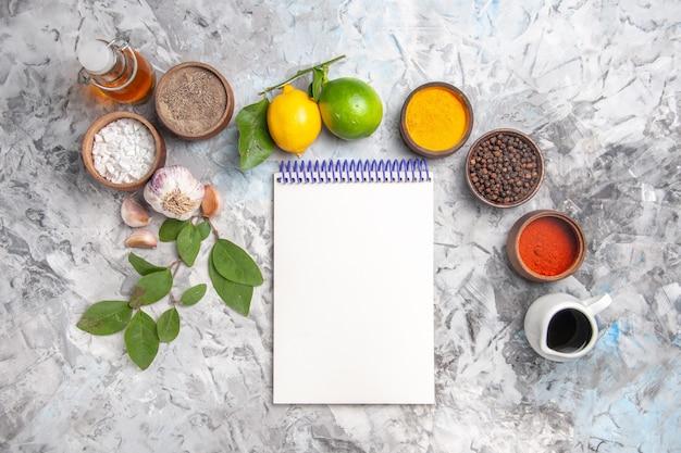 Vista dall'alto diversi condimenti con limone e aglio su olio da tavola bianco sale piccante di frutta
