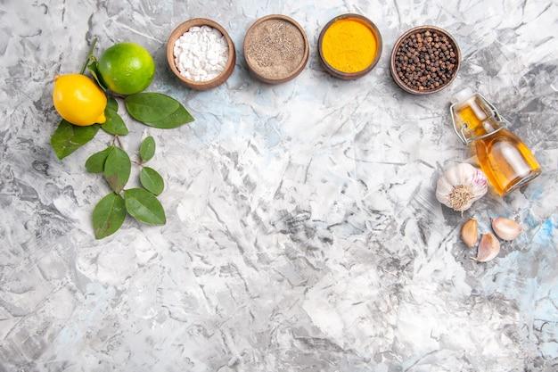 上面図白いテーブルにレモンとさまざまな調味料スパイシーなフルーツペッパーオイル