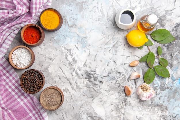 Vista dall'alto diversi condimenti con limone su olio da tavola bianco sale piccante di frutta