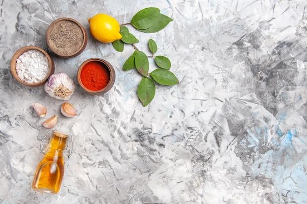 Vista dall'alto diversi condimenti con limone su tavola bianca olio piccante di pepe di frutta