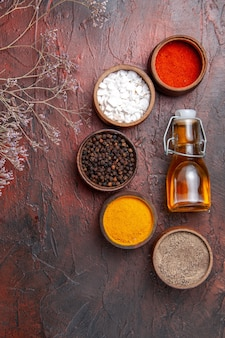 Top view of different seasonings with oil on dark surface