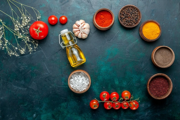 Top view different seasonings with oil and tomatoes on dark-green background ingredient product meal food vegetable
