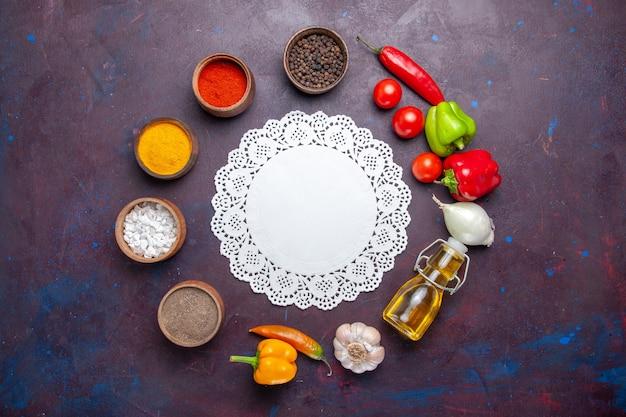 Vista dall'alto diversi condimenti con olio e verdure sulla superficie scura cibo pasto piccante vegetale