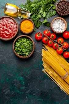 ダークデスクフードミール原料製品にオリーブオイルとフレッシュレッドトマトを使ったさまざまな調味料の上面図
