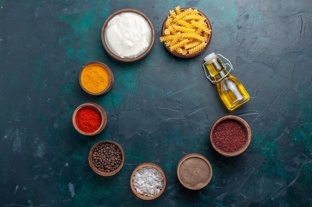 Вид сверху разные приправы с оливковым маслом и сырой итальянской пастой на темном столе