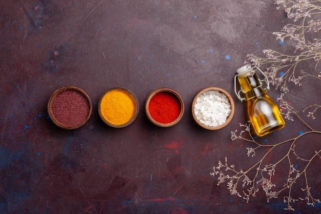 Вид сверху разные приправы с оливковым маслом на темном пространстве