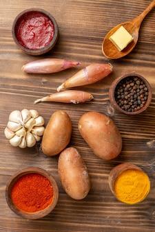 갈색 나무 책상에 감자와 마늘이 들어간 상위 뷰 다른 조미료 매운 초초 고추 익은