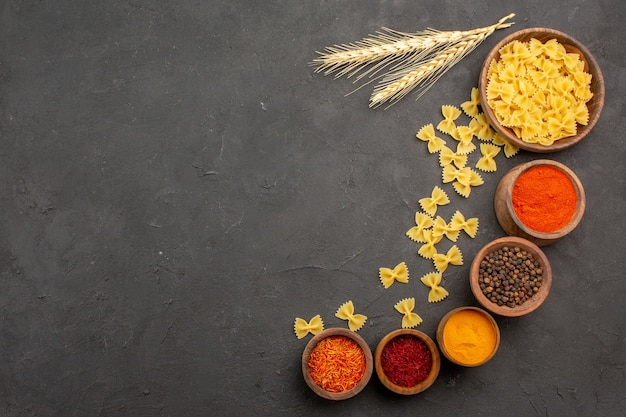 Top view different seasonings with raw pasta on dark background
