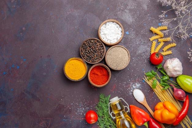 暗い背景に生パスタを使ったさまざまな調味料の上面図ローフードサラダ健康ダイエットパスタ