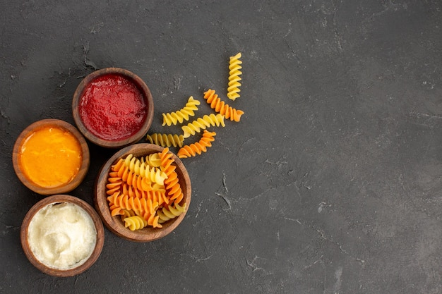 Top view of different seasonings with raw spiral pasta on black
