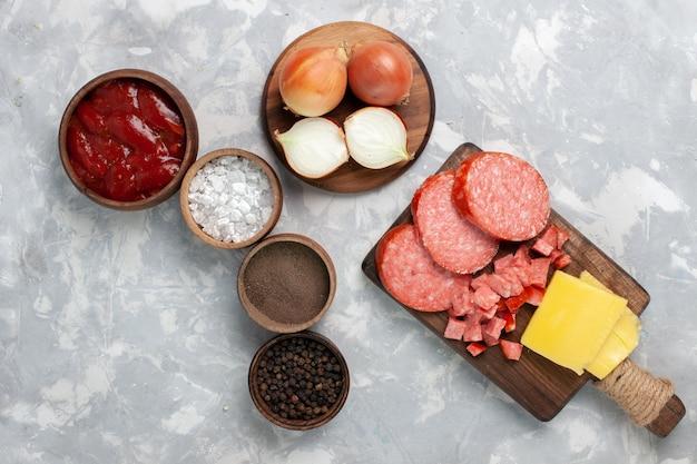 Vista dall'alto diversi condimenti con salsicce su bianco