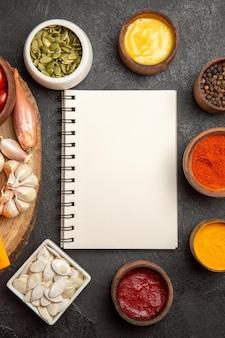 暗い背景の種のスパイシーな唐辛子の色の種とメモ帳でさまざまな調味料を上面図