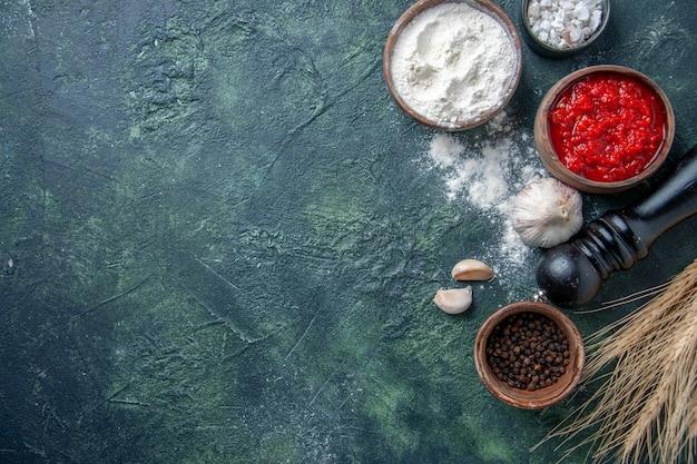 暗い背景にトマトソースと小麦粉を使ったさまざまな調味料の上面図トマト熟したサラダ野菜色生地ミール