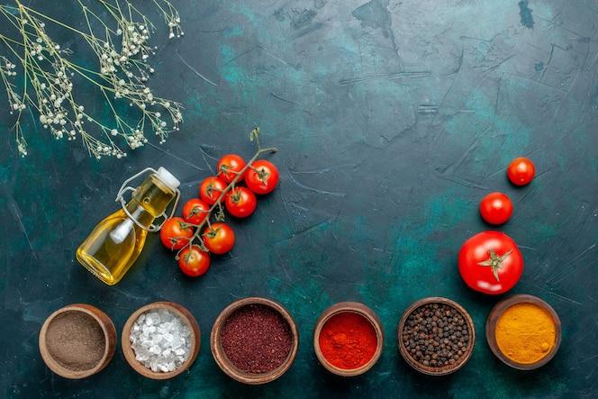 Вид сверху разные приправы с помидорами и маслом на темно-зеленом фоне, острый горячий ингредиент еды