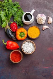 Vista dall'alto diversi condimenti con verdure su sfondo scuro insalata pasto prodotto alimentare