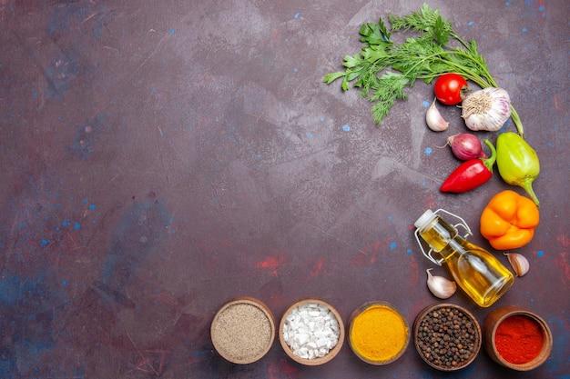 暗い背景の食事サラダ健康ダイエットの野菜とさまざまな調味料の上面図