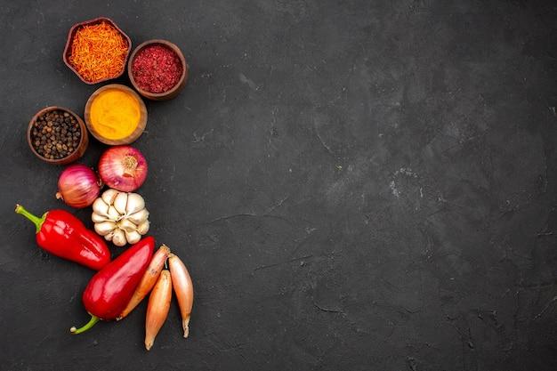 暗い背景に野菜とさまざまな調味料の上面図熟した食事野菜サラダ